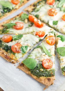 Spinach Pesto and Tomato Flatbread Pizzas - an easy dinner that you can have on your table in 30 minutes! These vegetarian pizzas are so good with a crispy whole wheat flatbread crust and crunchy pine nuts!