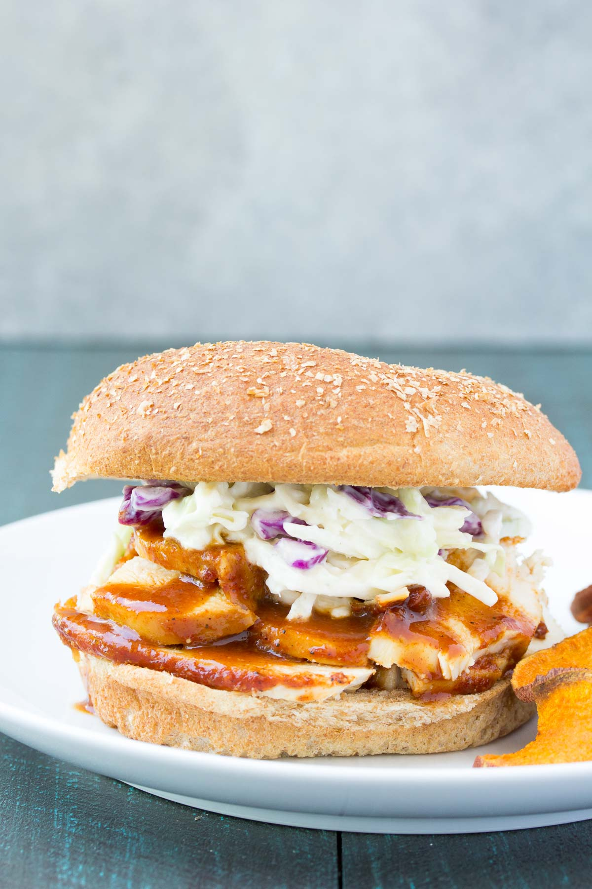 These Slow Cooker BBQ Chicken Sandwiches are an easy dinner that your family will love! The pulled chicken cooks in a homemade barbecue sauce in your crock pot. Plus, a recipe for easy, no mayo homemade coleslaw! These can be made into sliders for the perfect party food!