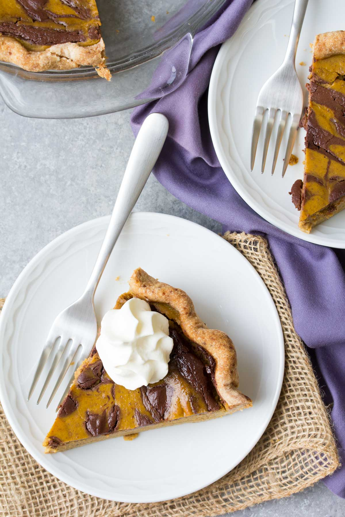 Swirled Chocolate Pumpkin Pie is our favorite Thanksgiving dessert! Make this healthier chocolate pumpkin pie for your holiday meal. Made with pure maple syrup, dark chocolate and a whole wheat crust. | www.kristineskitchenblog.com