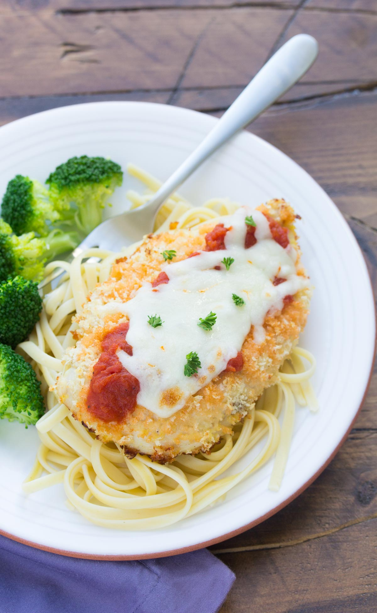 Lightened Up Baked Chicken Parmesan with linguine pasta and broccoli is an easy 30 minute meal! | www.kristineskitchenblog.com