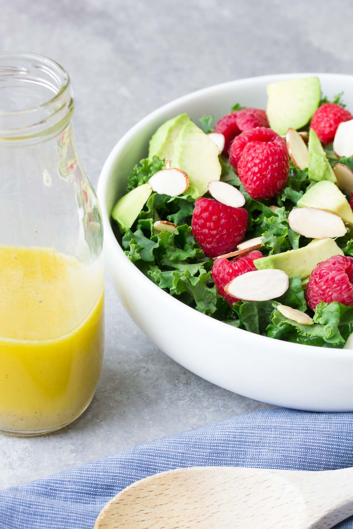 Quick, easy and healthy Avocado Kale Salad with Honey Lemon Dressing. With almonds and raspberries, tossed in a bright and tangy citrus dressing!