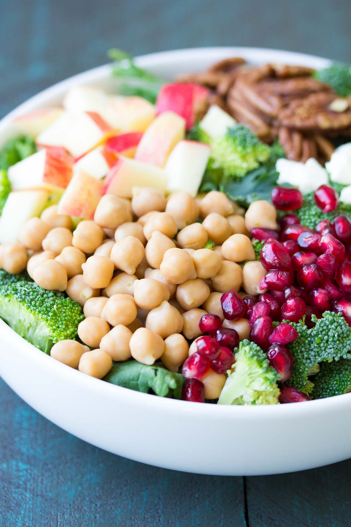 This Broccoli Kale Superfood Salad is a healthy holiday side dish. It's also delicious for lunch! With chickpeas, pomegranate seeds, apple, pecans and feta cheese.