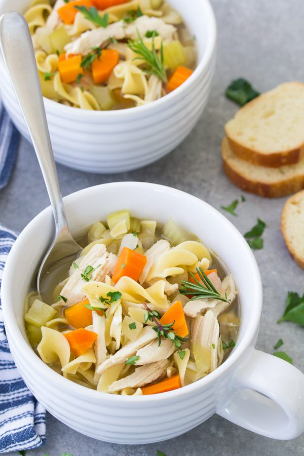 Homemade crock pot chicken noodle soup in a bowl with a spoon. Easy from scratch