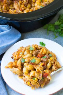 Easy Slow Cooker Taco Pasta on a plate with spoon and garnish