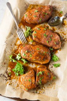 baked pork chops on baking sheet with parsley garnish
